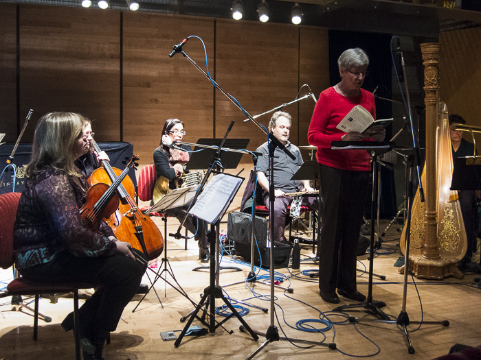 Jill MacLean reads her poem, Sable Island 44ºN 60ºW, to the audience with the musicians in the background.